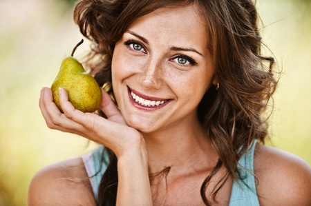freckled: Close-up portrait of pretty smiling dark-haired freckled woman wearing blue t-shirt, holding juicy pear at summer green park.
