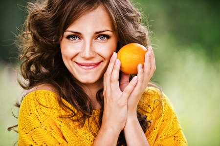 woman clothes: Portrait of pretty dark-haired woman holding juicy delicious orange at summer green park.