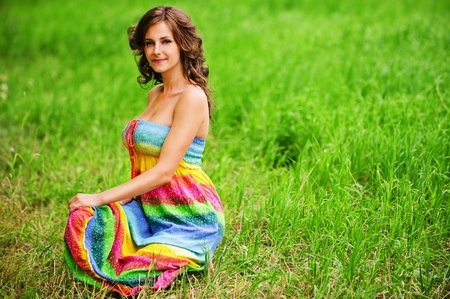 Portrait of young beautiful brunette woman wearing colourful bright dress, sitting on grass at summer green park. photo