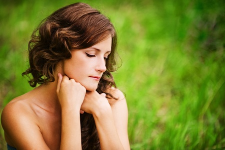 Portrait of pretty dark-haired curly woman sitting on grass at summer green park. photo
