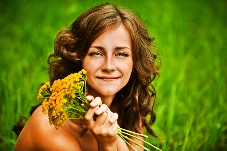 bouqet: Portrait of pretty dark-haired curly woman holding bouqet of yellow flowers, sitting on grass at summer green park.