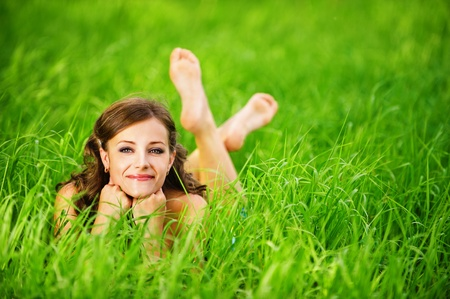 barefooted: Portrait of young beautiful brunette woman lying on grass and propping up her face at summer green park.