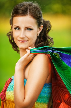 Portrait of young beautiful brunette woman wearing colourful top and holding many bags at summer green park. photo