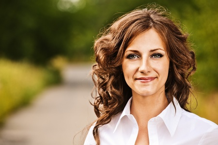 Portrait of beautiful young brunette woman wearing white blouse at summer green park.