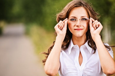 Portrait of pretty brunette young woman wearing eyeglasses and white blouse, standing at summer green park.