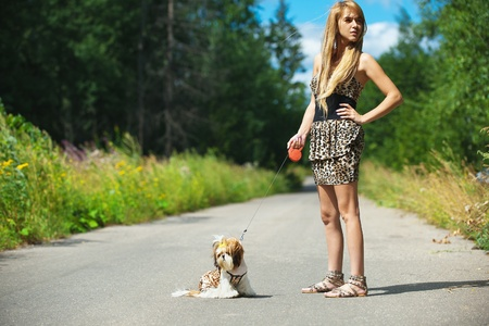 sidewards: young beautiful woman long hair short dress standing forest road with dog leash