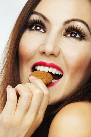 naked woman beautiful brown eyes, long hair looking up biting biscuit photo