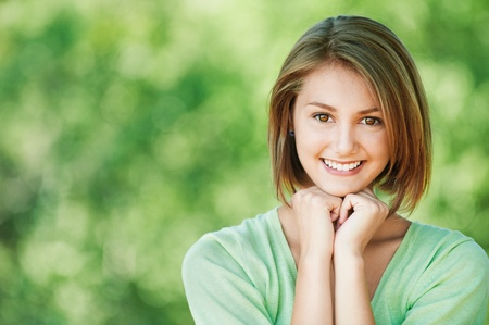 pretty young woman cheerful summer park short hair holding hands under chin Stock Photo