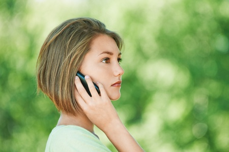 pretty serious young woman short hair profile talking phone summer park Stock Photo - 10672598