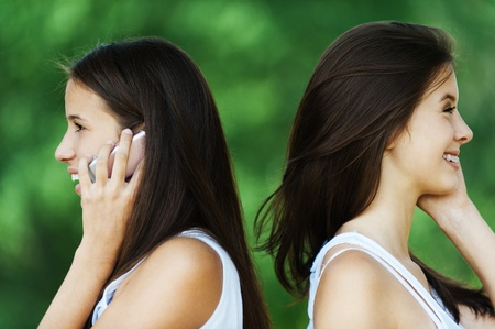 two beautiful long-haired woman profile standing behind each talk phone photo