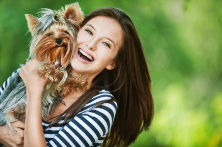 cute dogs: woman beautiful young happy with long dark hair in striped sweater holding small dog