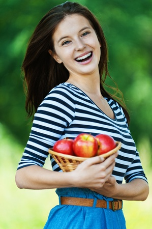 comestible: beautiful cheerful woman long hair holding basket apples summer park