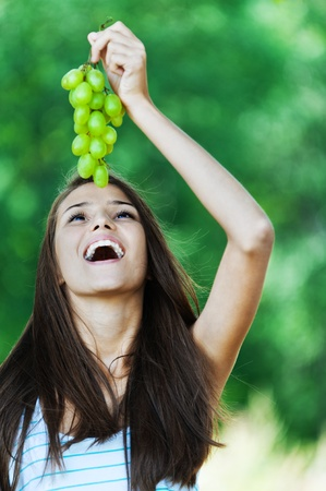 Attractive beautiful woman lifted her head up holding bunch grapes over mouth open photo