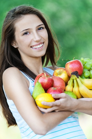 young woman is beautiful healthy wields lot of fruit photo