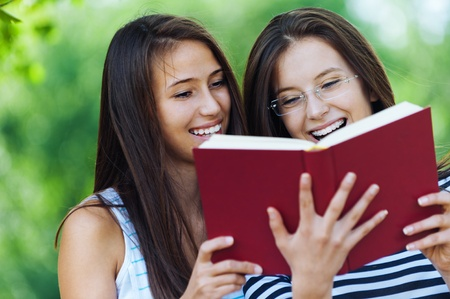 reading bible: Two women are cheerful beautiful young in the summer the park are holding red book, read Stock Photo