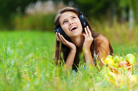 beautiful young woman lying grass clearing headphones fruit basket photo