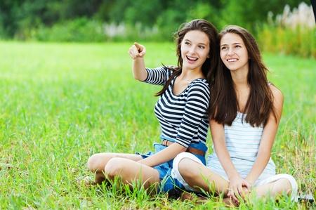 two sisters girlfriends long dark hair sitting cross-legged grass park talking photo