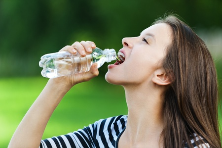 beautiful young woman in striped jacket standing in park summer drinks water from bottle photo