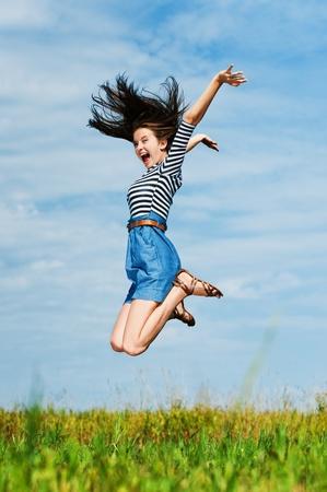 springende mensen: jonge mooie vrouw met lang haar op een zomerse dag in de wei springen hoog