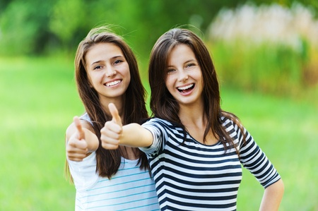 Two women friends beautiful smiles long dark hair standing next hand stretched front Stock Photo