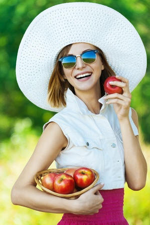 young woman sunglasses white hat holding basket red apples photo