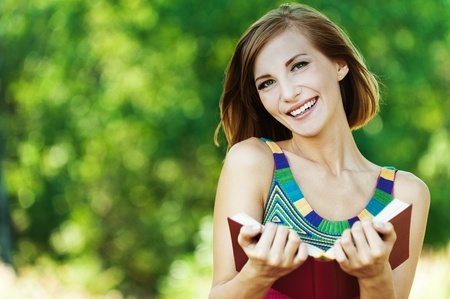 beautiful brunette penalty park reading book smiling Stock Photo - 10744313