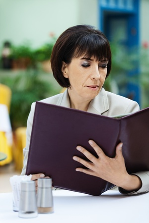 Beautiful brown-haired woman sitting cafe reading menu photo