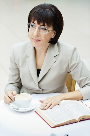 aside: woman wearing sitting cafe table drinking coffee reading book