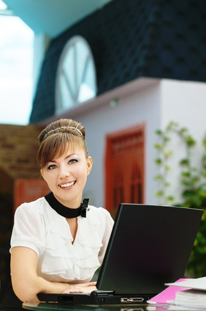 table skirt: young beautiful brunette table laptop smiling Stock Photo