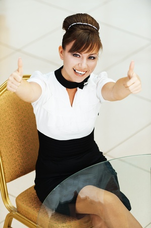 table skirt: cheerful beautiful young woman sitting table stretches arms forward Stock Photo