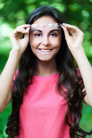 beautiful woman pink dress park raised glasses forehead Stock Photo - 10821687