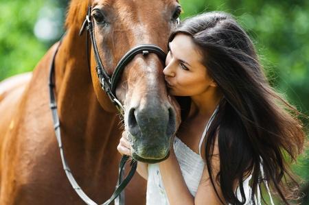 mujer en caballo: mujer de pelo largo beso hermoso caballo