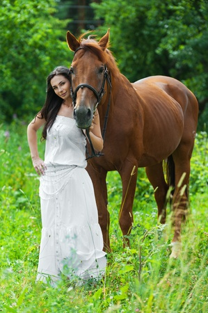 pretty young woman long-haired long white dress next horse photo