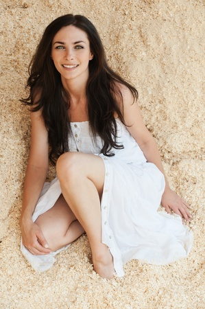 portrait lovely young woman sitting sand bare feet wearing white dress photo