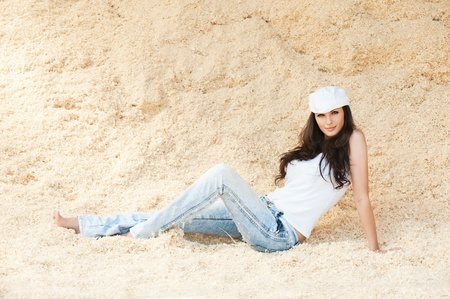 beautiful woman long hair jeans white cap sits sand photo
