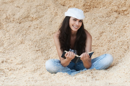 beautiful young woman white hat jeans sitting sand reading book photo