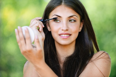 portrait beautiful young woman bare shoulders looks mirror paints eyelashes background summer green park Stock Photo