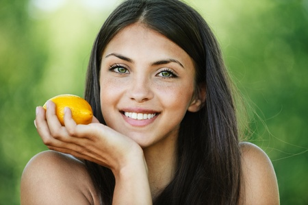 carnal: beautiful young woman long-haired brunette background summer park smiling holding lemon