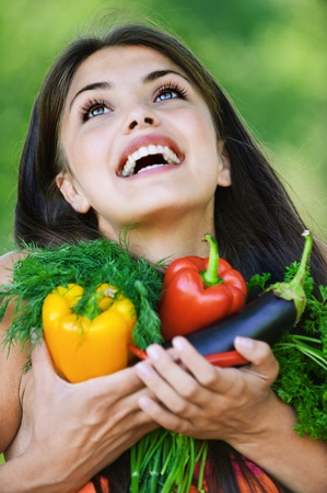 portrait pretty young cheerful woman vegitorianka holds lot vegetables looking up background green park photo