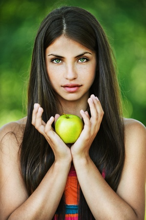 portrait pretty serious long-haired woman hands yellow apple background summer park Stock Photo