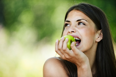 portrait young charming brunette woman biting green apple background summer park