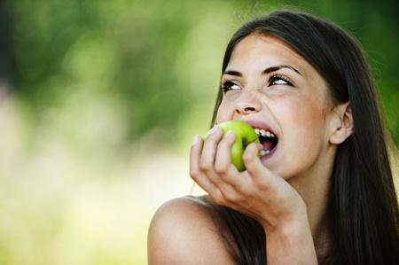 sidewards: portrait young charming brunette woman biting green apple background summer park