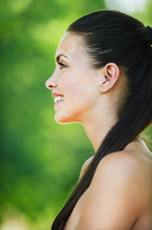 carnal: portrait charming woman profile long dark hair bare smiling background green park