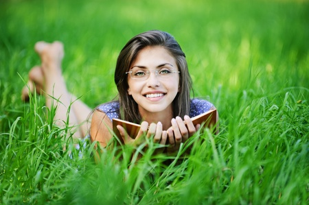 pretty young woman glasses lying green grass reading book background green meadow photo