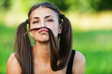 portrait cheerful funny young woman hairstyle two long tail background summer park photo