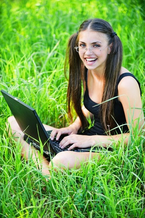 gay pretty young long-haired woman glasses sitting grass laptop background green meadow photo