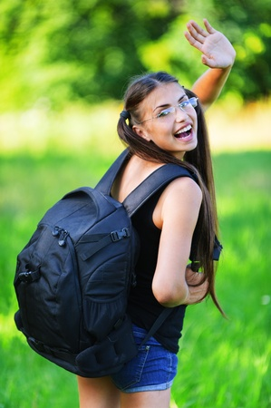 attractive woman glasses rucksack back smiling waving hand background summer green park photo