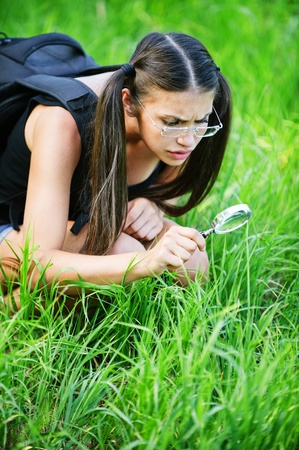 serious pensive woman glasses sitting magnifying glass grass background green meadow photo