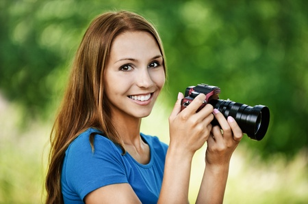 portrait beautiful young woman smiling holding camera background summer green park Stock Photo