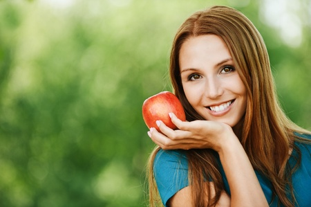 portrait pretty smiling woman vegetarian red apple hand background summer green park Stock Photo - 11032797
